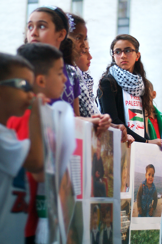 Several children hold posters with photographs of the children who have recently died in Gaza.