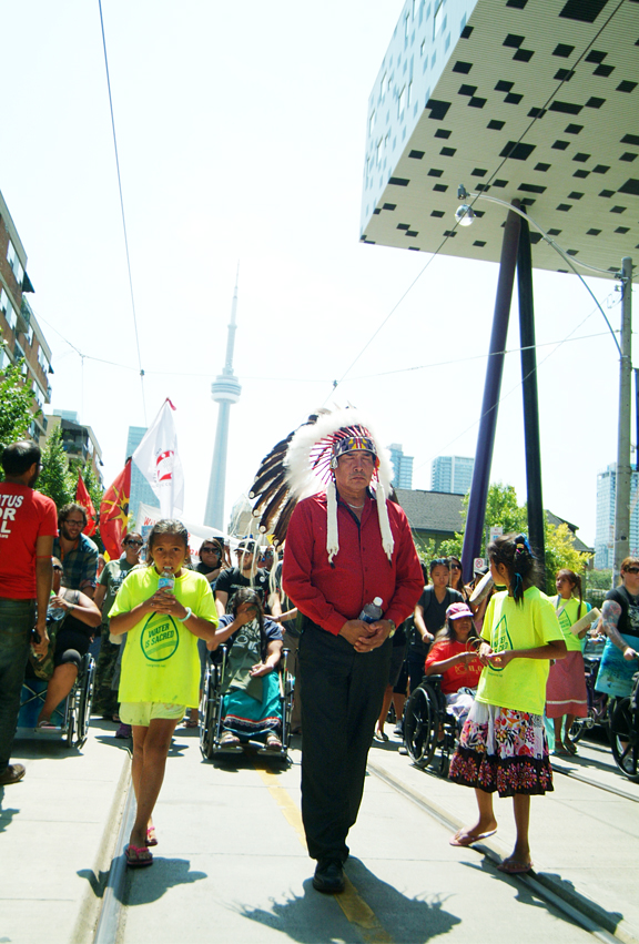 First Nations Chief with headdress walking in street with CN Tower and crowd of people in background