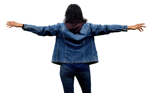 Photograph of woman standing with her back to viewer, wearing casual clothes, jean jacket, hands outstretched