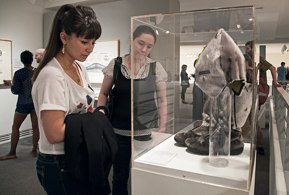 Two women viewing seal skin boots behind glass case