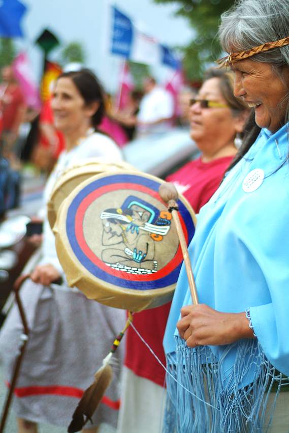 Three women marching. One woman smiling and drumming on a traditional First Nations hand drum.