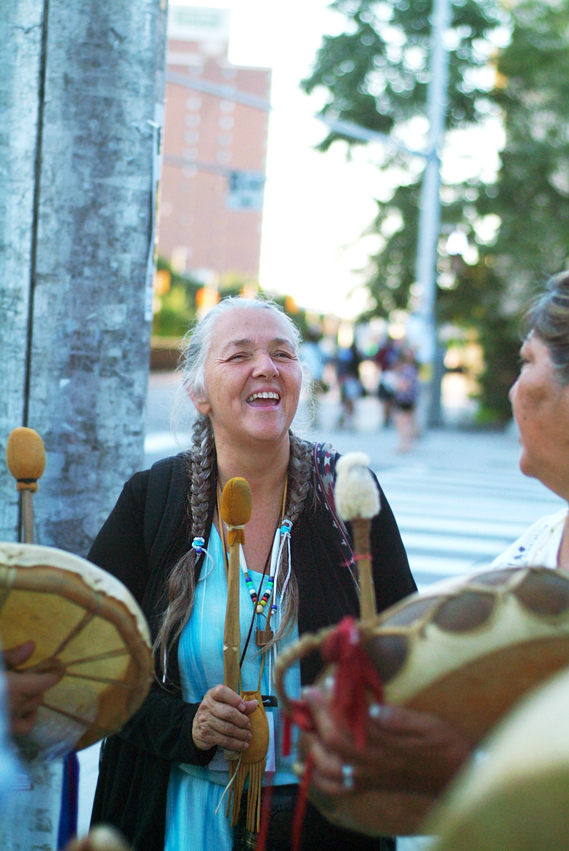 Women standing on city street corner drumming and smiling