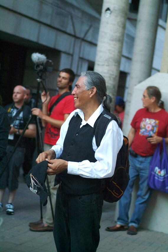 Man with long hair and pony tail smiling in crowd of men. One holding a video camera and microphone