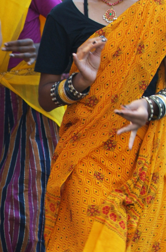 torso of young woman dancing with hands in pose and wearing sari