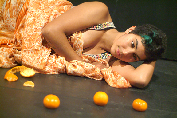 Young East Asian woman lying on floor wrapped in a sari with oranges and orange peels around her