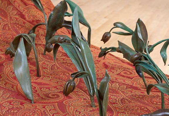 Upclose shot of bronze cast drooping tulips rising from a paisley upholstered couch