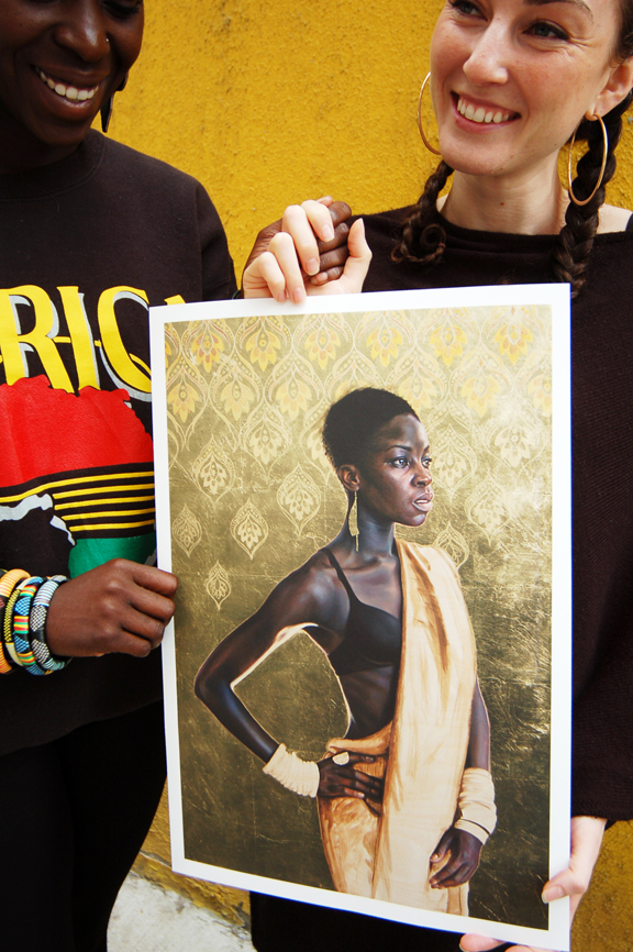 Two young women, one black, one white, holding hands and a print of a painting of the black woman