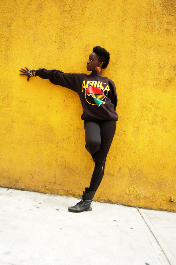 Young black woman leaning against a yellow stucco wall with her right arm outstretched, wearing a shirt that says AFRICA
