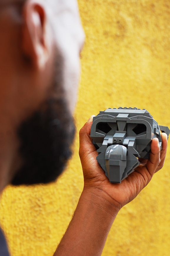 Side profile of a young black man looking at a lego monkey head he is holding in his hand
