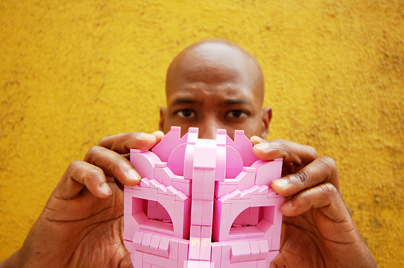 upclose shot of black man's hands holding a pink lego mask and peering over it
