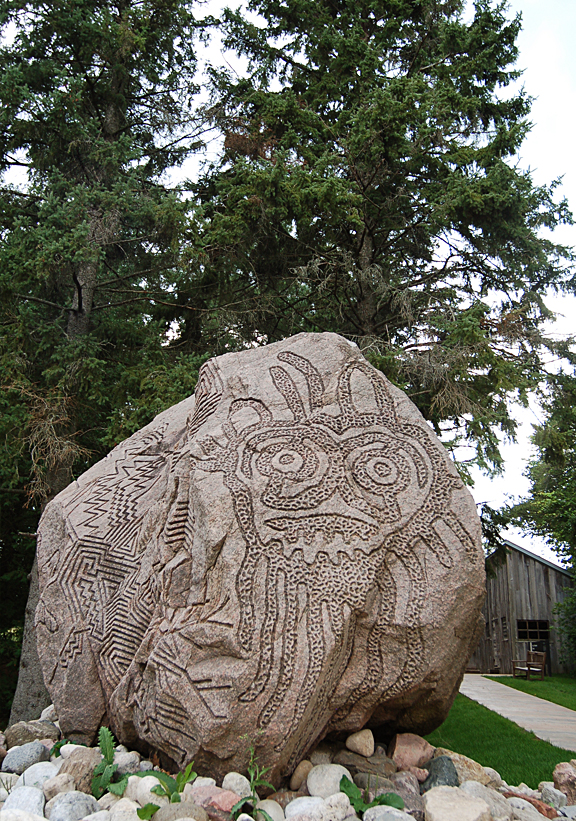 Stone carving on large boulder with wood cabin and trees in the background