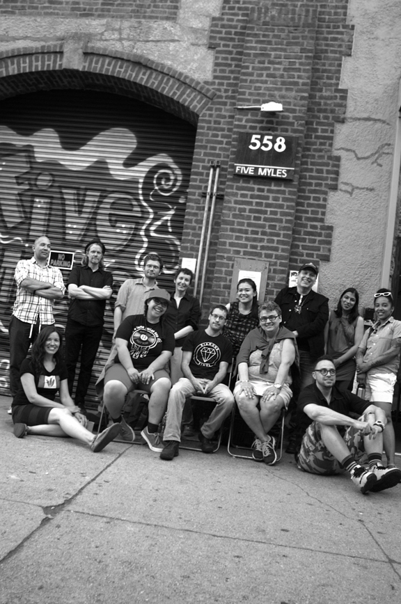 group of people sitting and sanding in front of brick building